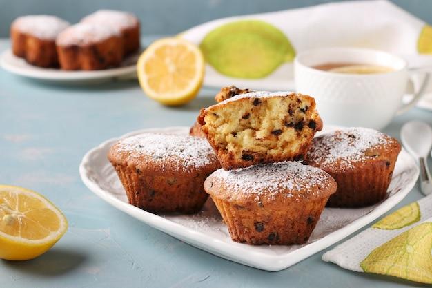 Muffins au citron maison avec du chocolat sur une plaque blanche sur une surface bleue