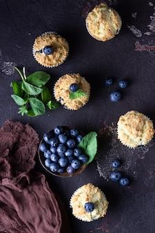 Muffins aux bleuets avec des baies fraîches et des feuilles de menthe sur pierre brune foncée.