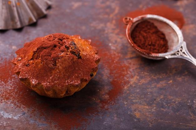 Muffins aux bleuets, garnis de poudre de cacao, sur fond sombre.