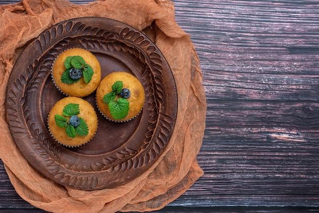 Muffins aux bleuets en plaque brune sur bois foncé. vue de dessus.