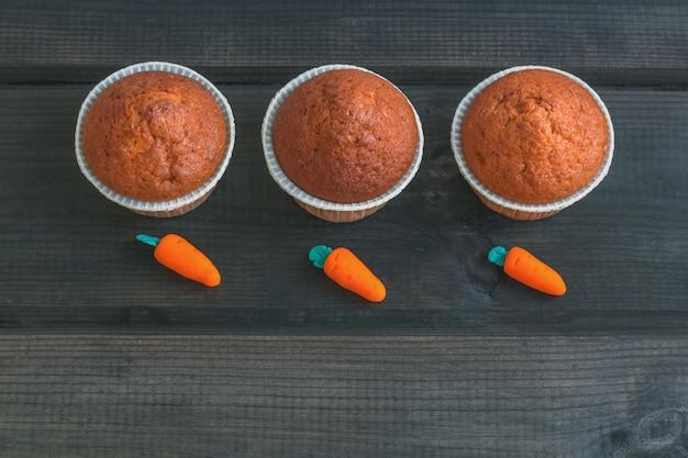 Muffins aux carottes fraîchement cuits décorés de carottes en massepain sur fond de bois. journée nationale du gâteau aux carottes.