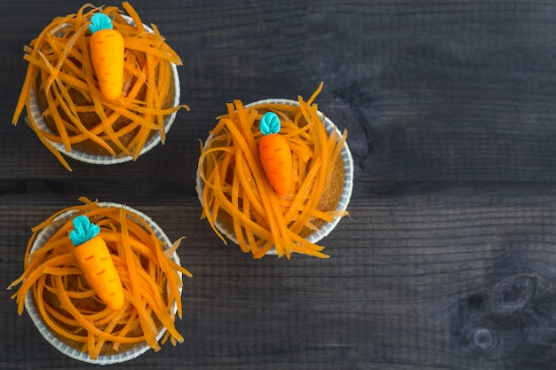 Muffins aux carottes fraîchement cuits décorés de croustilles de carottes fraîches et de carottes en massepain sur fond de bois. journée nationale du gâteau aux carottes.