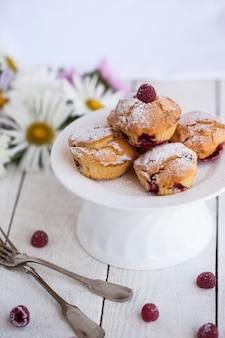 Muffins aux framboises, saupoudrés de sucre en poudre