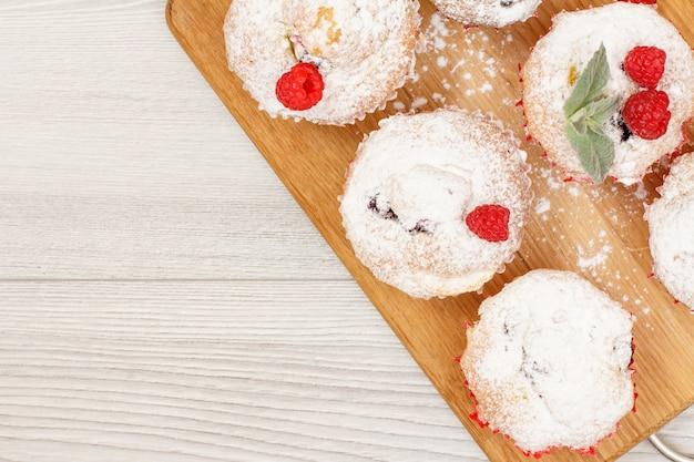 Muffins aux fruits faits maison saupoudrés de sucre en poudre et de framboises fraîches sur une planche à découper en bois. bonbons et pâtisseries de noël. vue de dessus avec espace de copie.