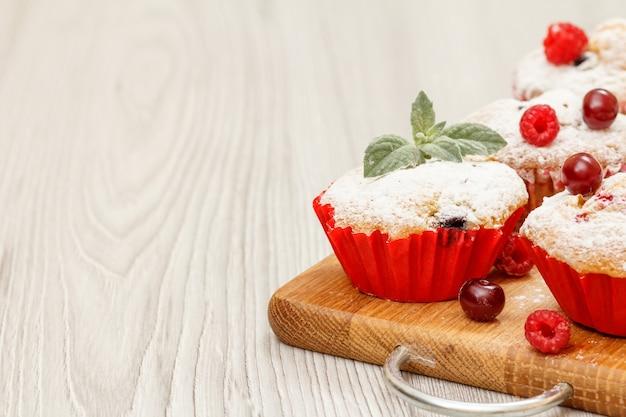 Muffins aux fruits faits maison saupoudrés de sucre en poudre et de framboises fraîches sur une planche à découper en bois. bonbons et pâtisseries de noël.