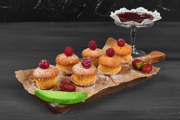 Muffins aux fruits rouges sur une planche de bois.