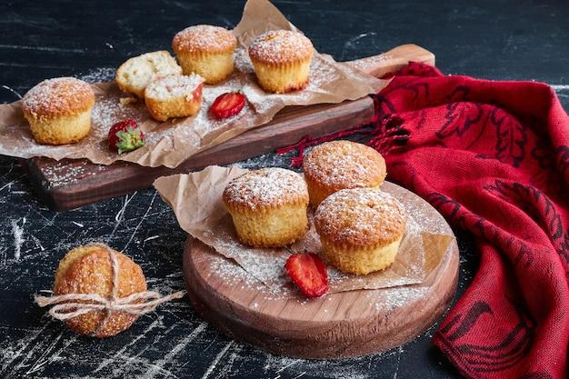 Muffins aux fruits rouges sur des planches en bois.