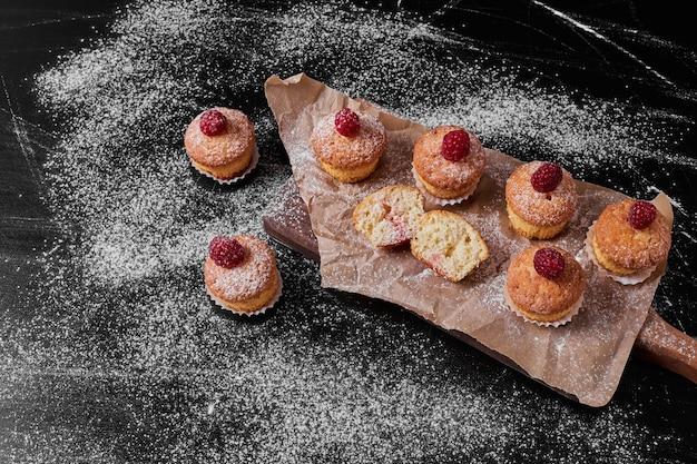 Muffins aux fruits rouges sur un plateau en bois.