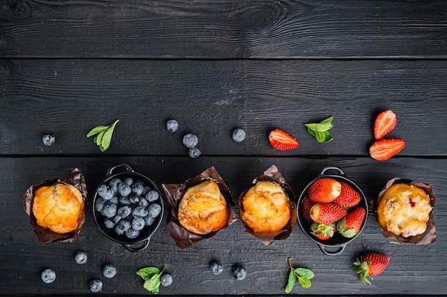 Muffins aux myrtilles, sur table en bois noir, vue de dessus à plat