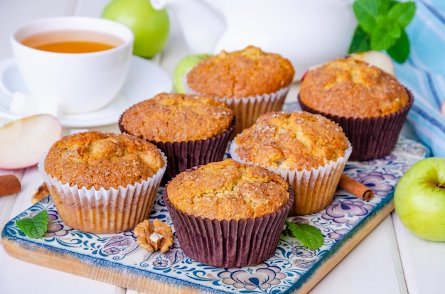 Muffins aux pommes croustillants faits maison avec noix et cannelle sur bois blanc