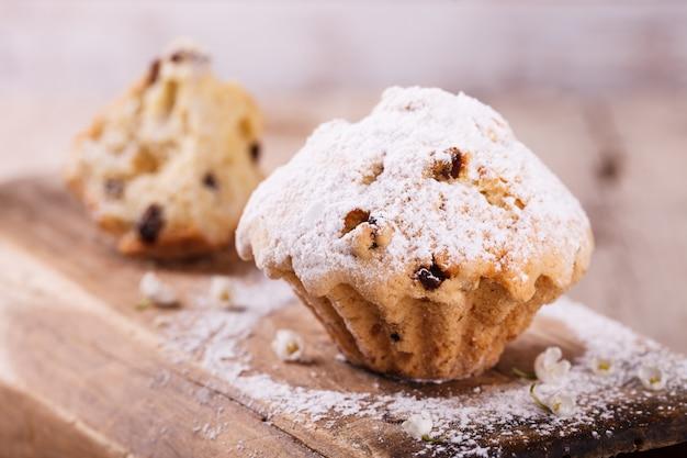 Muffins aux raisins secs saupoudrés de sucre en poudre.
