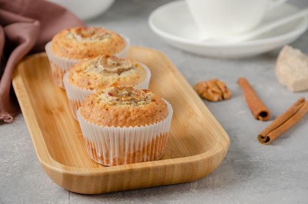 Muffins à la banane avec des noix d'avoine et de la cannelle sur une plaque en bois sur fond de béton gris