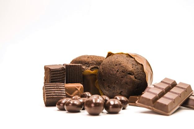 Muffins; barre de chocolat et boules sur fond blanc