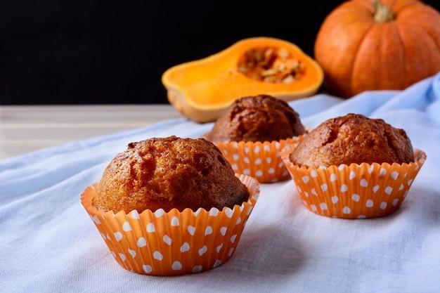Muffins à la citrouille dans les enveloppes orange sur la serviette bleue
