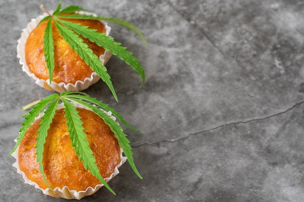 Muffins cupcake au cannabis et feuilles sur fond gris foncé