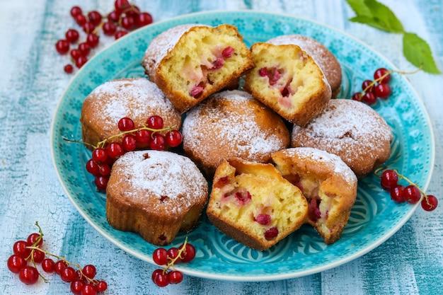 Muffins faits maison avec des baies, saupoudrés de sucre en poudre, disposés sur une table en bois bleue, style rustique