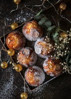 Muffins faits maison avec du sucre en poudre sur un fond sombre
