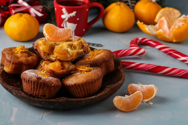 Muffins faits maison avec des mandarines, saupoudrés de sucre en poudre est situé sur le fond bleu clair du nouvel an ou de noël, gros plan