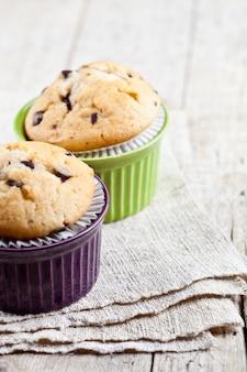Muffins frais faits maison sur des bols en céramique sur une serviette en lin sur une table en bois rustique.