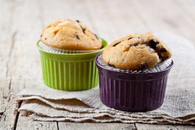 Muffins frais faits maison sur des bols en céramique sur une serviette en lin.