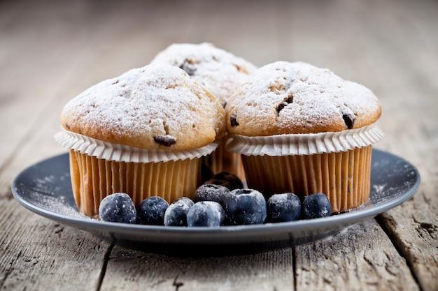 Muffins frais faits maison avec du sucre en poudre et des bleuets sur une plaque en céramique sur une table en bois rustique.