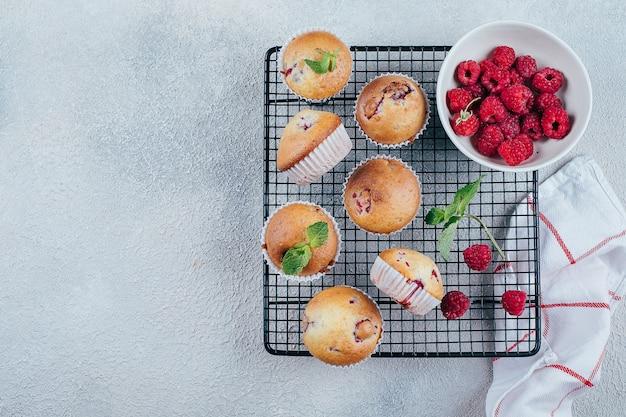 Muffins framboises et baies sur un gril métallique refroidissant sur du béton léger. vue de dessus, espace de copie
