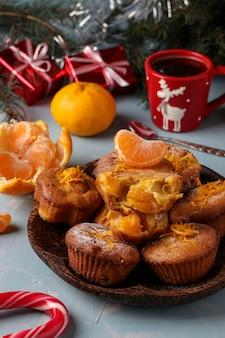 Muffins maison aux mandarines, saupoudrés de sucre en poudre est situé sur le fond bleu clair du nouvel an ou de noël, gros plan, orientation verticale