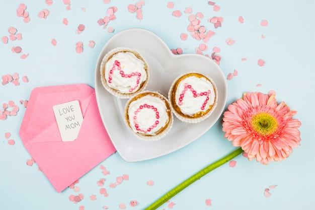 Muffins avec mot maman sur plaque près de fleur et enveloppe avec étiquette entre confettis