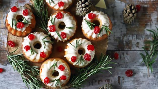 Muffins de noël au romarin, glaçage blanc et fruits rouges. gâteaux de vacances élégants. composition de noël.