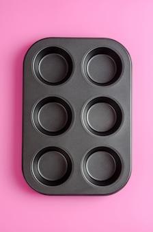 Muffins et petits gâteaux allant au four sur un fond rose.