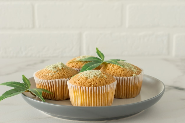 Muffins sains et savoureux végétaliens et sans gluten d'affilée garnis de graines de chanvre sur une table en marbre. muffins cupcake à la marijuana avec des feuilles de cannabis.