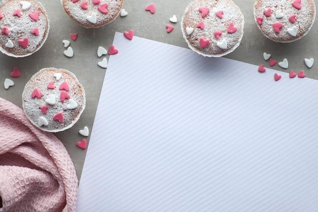 Muffins saupoudrés de sucre avec des coeurs de glaçage fondant rose et blanc, texte