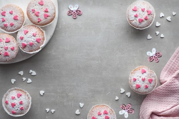 Muffins saupoudrés de sucre avec des cœurs glaçants fondants roses et blancs