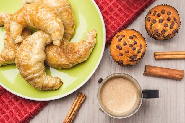 Muffins, tasse de café, cannelle et croissant