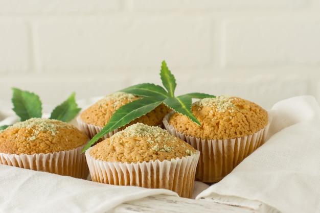 Muffins végétaliens et sans gluten sains et savoureux garnis de graines de chanvre sur une plaque blanche sur une table en bois. muffins cupcake à la marijuana avec des feuilles de cannabis.
