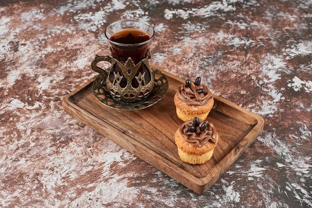 Muffins et un verre de thé sur une planche de bois.