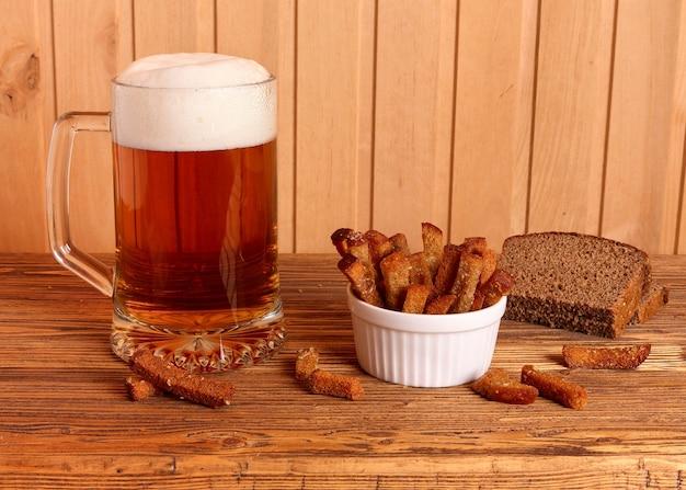 Mug avec de la bière légère et des craquelins salés sur une table en bois