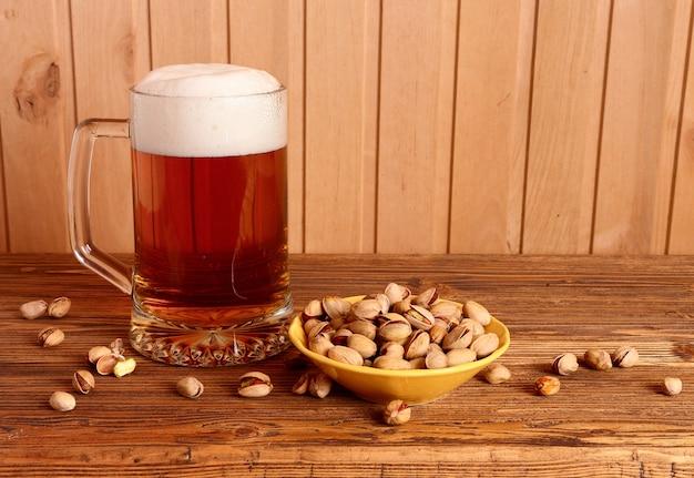 Mug avec bière légère et pistaches sur table en bois