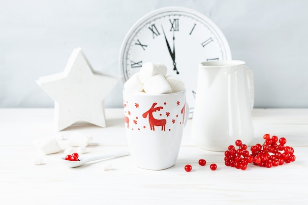 Mug blanc avec boisson chaude et guimauves, baies de viorne rouge, pichet et horloge.