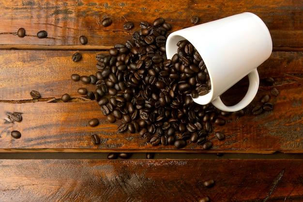 Mug blanc avec des grains de café torréfiés et frais versé sur une table en bois rustique