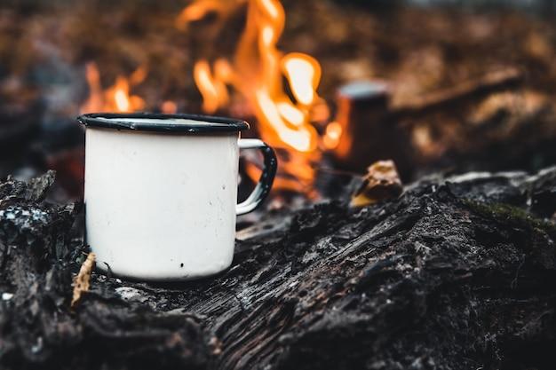 Mug blanc près de feu de joie dans la forêt