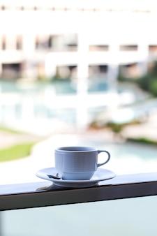 Mug blanc sur soucoupe blanche avec café sur la piscine extérieure sur place