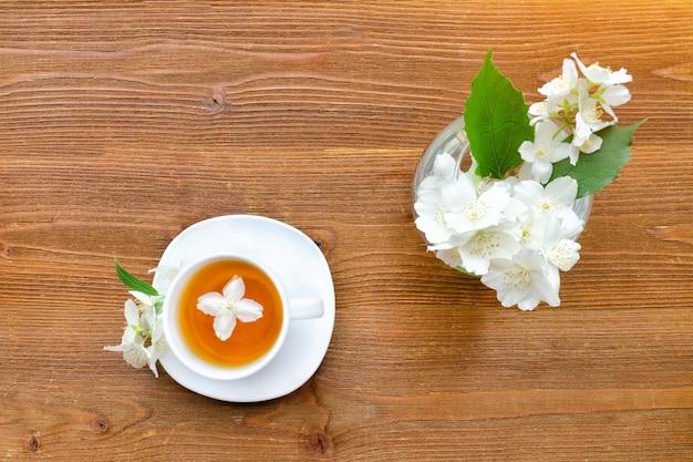 Mug blanc de thé vert et un vase au jasmin. table en bois.