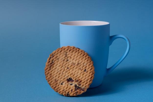 Mug bleu et cookie sur un fond bleu.