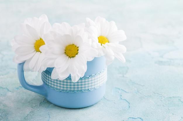 Mug bleu avec marguerites sur une surface de béton minable