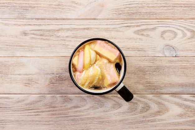 Mug avec chocolat chaud et guimauves sur table en bois.