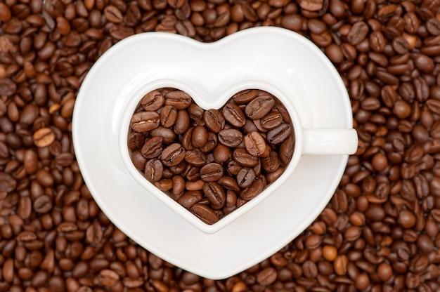Mug coeur blanc rempli de grains de café sur une soucoupe blanche avec des grains de café