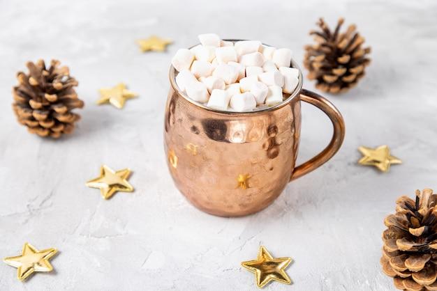 Mug en cuivre avec du cacao ou du chocolat et des guimauves sur le dessus, des étoiles d'or et des pommes de pin décoration de noël