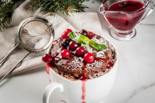 Mug cupkake au chocolat dans une tasse en céramique, avec canneberge et sauce