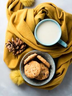 Mug avec du lait et des biscuits dans une écharpe d'hiver douce